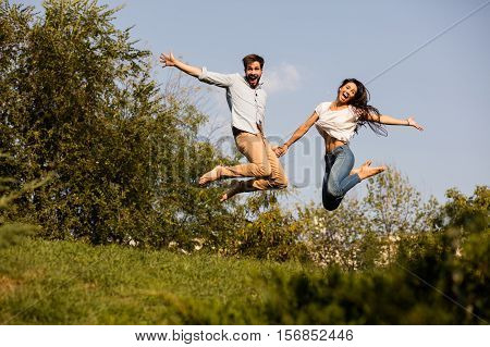 Young Couple Jumping Somewhere In Nature