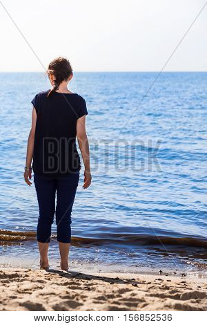 Young woman seen from back stand barefoot at the seashore