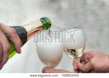 Wine is poured from a bottle into glasses