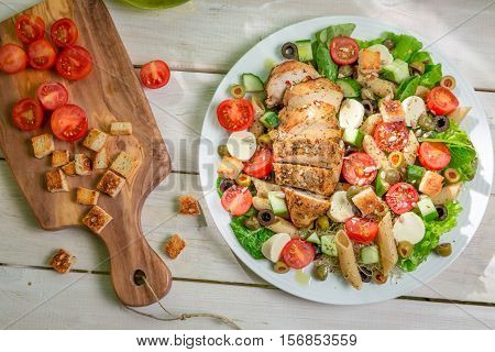 Salad With Chicken And Vegetables On Old Wooden Table