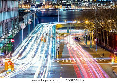 Light trails on the busy night streets, crossroad in big city, long exposure motion. New York City, USA