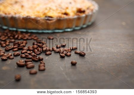 Coffee beans. Homemade pie. Coffee beans scattered on the kitchen counter