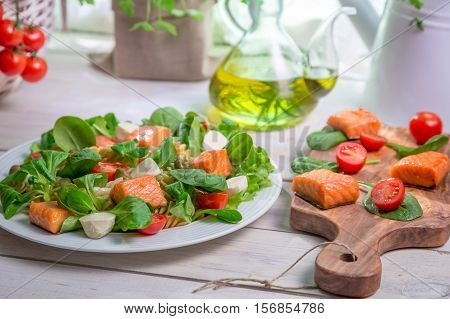 Salad With Salmon, Spinach And Mozzarella On Old Wooden Table