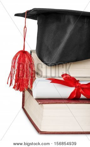 A graduation mortarboard on top of a stack of books, with parchment scroll tied in red ribbon