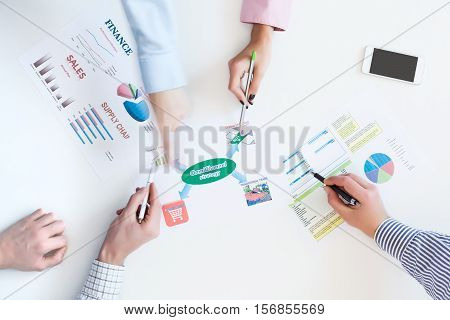 Group of Business People discussing new Product Strategy top View Business Meeting with Paper Charts on White Desk Hands pointing with pens