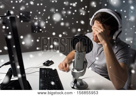 technology, gaming, entertainment, let's play and people concept - close up of sad young man in headset with pc computer playing game at home and streaming playthrough or walkthrough video over snow