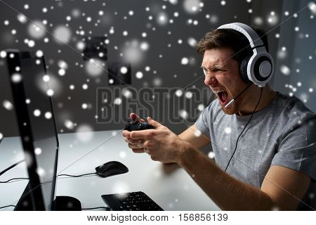technology, gaming, entertainment, let's play and people concept - angry screaming young man in headset with controller gamepad playing computer game at home and streaming playthrough video over snow
