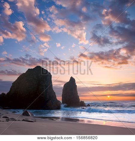 Ocean Landscape at Sundown romantic time,  big rocks and stones beach. Portugal, Europe