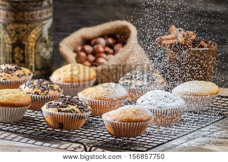 Falling Powder Sugar On Vanilla Muffins On Old Wooden Table