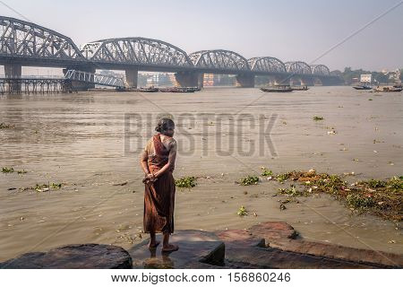 An old woman watches high tide water flow in the ganges river at Dakshineshwar. The Bally bridge (Vivekananda Setu) at the backdrop.