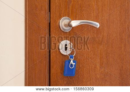 door handle with inserted key in the keyhole with blue keyholder