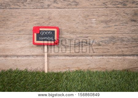 Good Morning signpost in beautiful greensward on wooden background