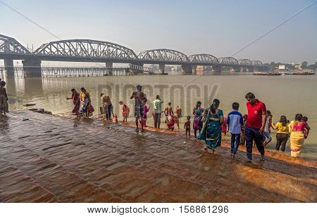 People gather at the Dakshineswar temple ghat close to Bally bridge on the banks of the river Ganges as part of a hindu ritual on purnima (full moon) day to bathe or sprinkle ganga water. Photograph taken on November  13, 2016