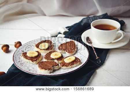 Delicious Sweet Breakfast With A Cup Of Tea, And Waffles With Chocolate Spread, Bananas And Marshmal