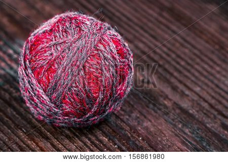 Single ball of wool of purple color on the wooden table..