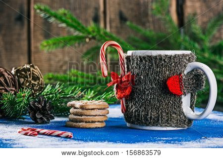 Mug with woolen warmer holding candy cane on the table with christmas decorations