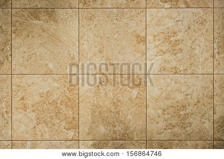 Marble floor or wall square tile pattern. Ochre brown texture.