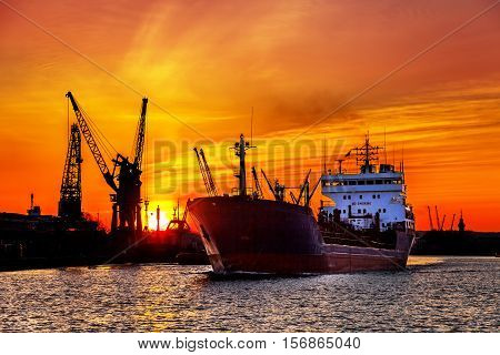 Ship and cranes at sunset in port of Gdansk Poland.