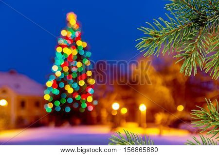 Christmas background with unfocused Christmas tree and snow by night