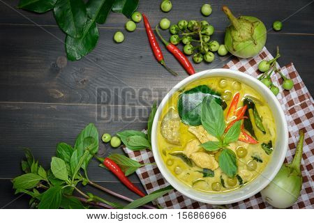 green curry with chicken (Kang Keaw Wan Gai) with brown tablecloth and vegetable on wooden background top view Thai local food