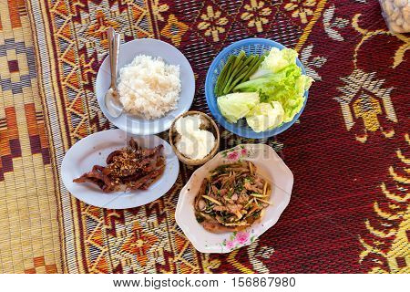 Traditional Thai spicy lunch with chicken,pork and sticky rice on a rush mat