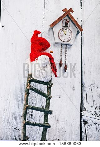 Handmade yarn snowman standing on the toy ladder and wathing to the  toy clock on the white wall. concept of christmas advent