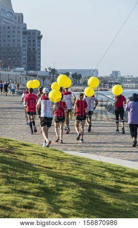 Haifa, Israel-10 September, 2016 : Group of people with yellow balloons jogging along the promenade near the sea in Haifa, Israel