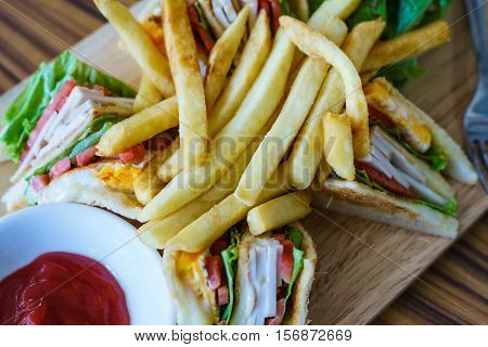 American Classic food Clubhouse sandwich with french fries and ketchup in close up