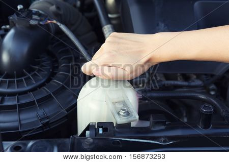 Asian girl's hand checking level of coolant car engine.
