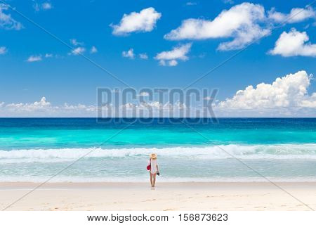 Lone woman wearing white tunic and beach hat, enjoying amazing view of Police Bay on Mahe Island, Seychelles. Summer vacations on picture perfect tropical beach concept.