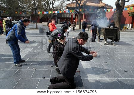 BEIJING - FEBRUARY 25: Worshippers holding incense sticks pray at Yonghegong Lama Temple in Beijing, China, February 25, 2016.