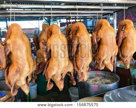 braised duck hung on an iron railing waiting for the market.