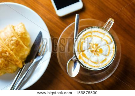 White coffee cup on wooden table on coffeeshop with smartphone in backgound