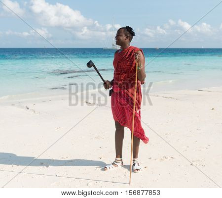 ZANZIBAR, TANZANIYA- JULY 17: smiling masai on a beach and blue sea on the background on July 17, 2016 in Zanzibar