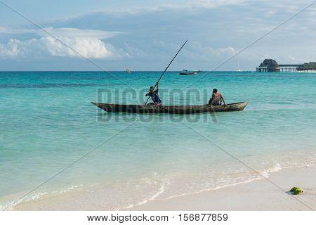 ZANZIBAR, TANZANIYA- JULY 17: people and wooden fishing ship in water near fishing village on July 17, 2016 in Zanzibar