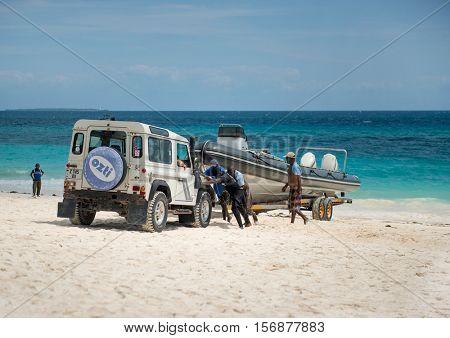 ZANZIBAR, TANZANIYA- JULY 18: jeep pulling yacht to sandy shoreon July 18, 2016 in Zanzibar