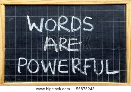The phrase Words Are Powerful written by hand in white chalk on a blackboard as a reminder of the power of communication and language