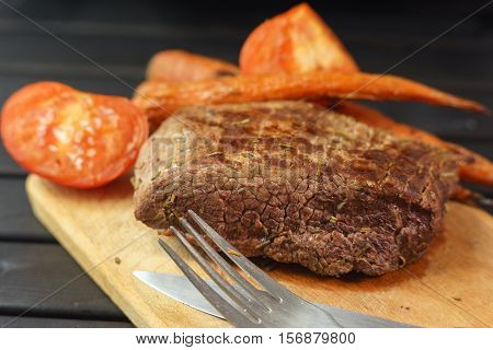 Roasted steak from beef on a woden board with grilled vegetables