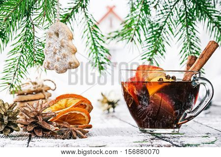 Cup of tea with apple and orange pieces, dried orange slices, cones and spices under evergreen branches