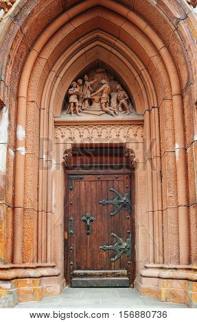 wooden doors with metal hinges and a beautiful arch.