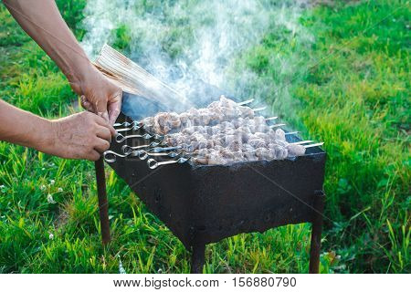 shish kebab is fried on coals in the yard on summer day