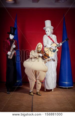 not understandable creatures freaks musicians. Three girls or boys with Halloween face mask on red background.