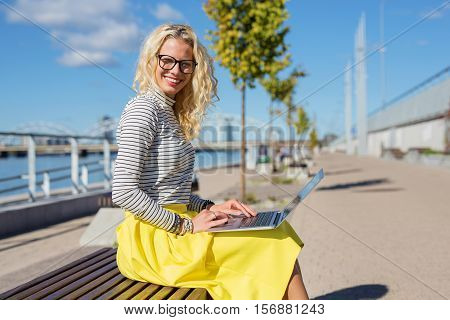 Stylish woman sitting ouside and working on laptop
