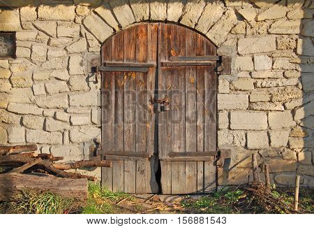 Gray old surface with doors at the sunlight. Ancient stable