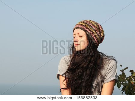 young woman with eyes closed breathing fresh air on sea background