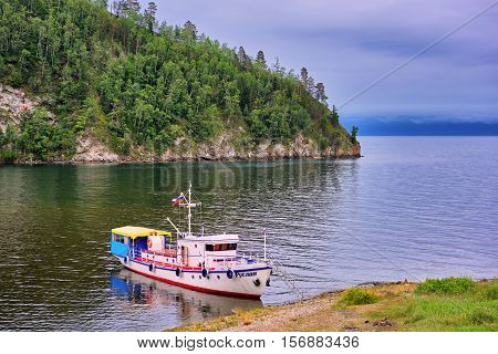 LAKE BAIKAL IRKUTSK REGION RUSSIA - July 28.2016: Baikal landscape with a walking yacht on shore of small bay. Vehicles for transport of leisure travelers and walks on water of Lake Baikal.