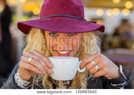 Happy and flirty woman drinking hot beverage