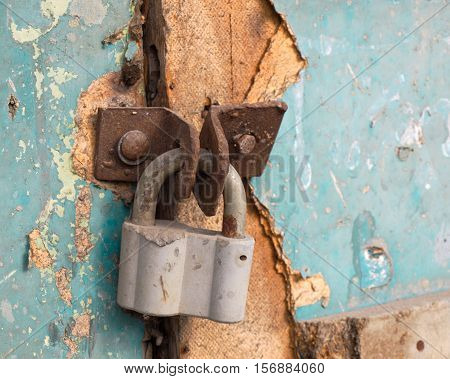 Locked metal padlock on old weathered door