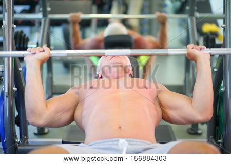 Middle-aged strong man in pants raises bar in modern gym, shallow dof