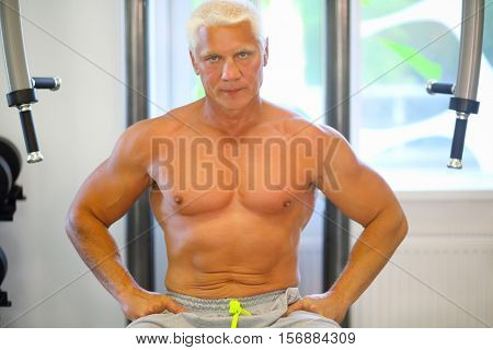Middle-aged strong man in pants rests after training in modern gym, shallow dof